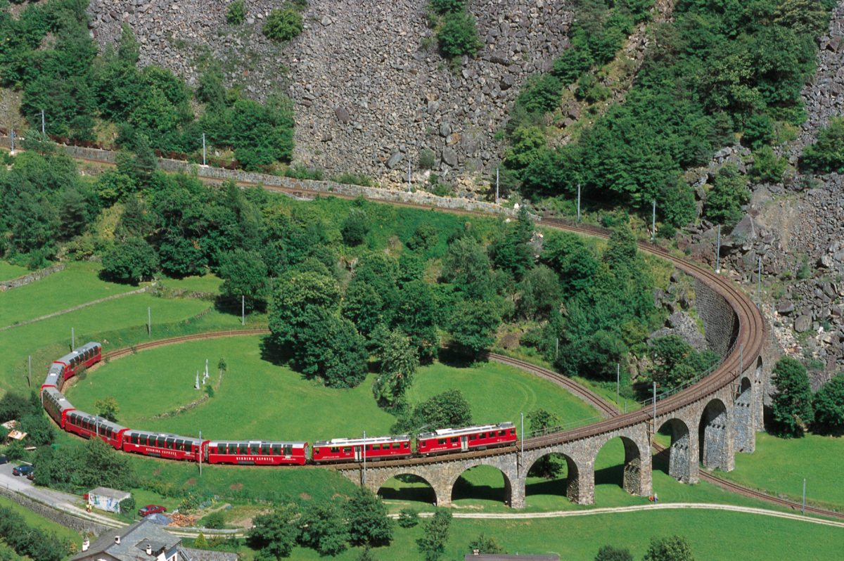 The Rhaetian Railway in the Albula / Bernina Cultural Landscape. Bernina Express with panorama cars on the circular viaduct at Brusio. Rhaetische Bahn in der Kulturlandschaft Albula / Bernina. Bernina Express mit Panoramawagen auf dem Kreisviadukt bei Brusio. Il Bernina Express con carrozze panoramiche sul viadotto elicoidale presso Brusio. Bernina Express avec wagon panoramique sur le viaduc helicoidal pres de Brusio. Copyright by: RhB By-Line: swiss-image.ch/Peter Donatsch